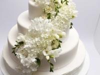 Baltā kāzu torte ar hortenzijām, frēzijām un rozēm