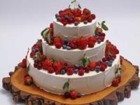 Trīsstāvu kāzu kūka uz koka ripas
