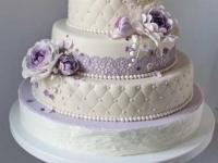 Baltai kāzu tortei violeti ziedi un mežģīnes