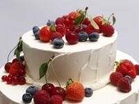 Kāzu torte ar dekoratīvu sviesta krēma apdari un ogām