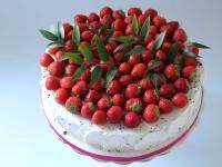 Vienstāvu kāzu torte dekorēta ar svaigām zemenēm un zaļumiem