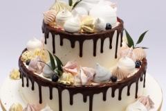 Kāzu torte ar sokolādes maliņām, bezē un zaļo lapu dekoru