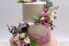 Četrstāvu Kāzu torte ar perlamutra un violetu krāsojumu un ziediem.