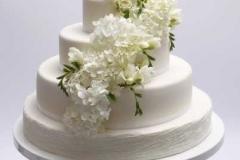 Baltā kāzu torte ar hortenzijām, rozēm un frēzijām