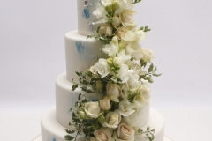 Četrstāvu kāzu torte ar baltiem un vanilas krāsas ziediem