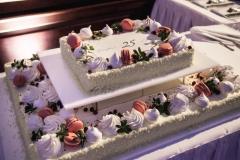 Divstāvu korporatīvā torte ar bezē, makarūnu un zaļumu dekoru.