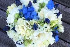 Līgavas pušķis ar baltiem un ziliem pavasara ziediem