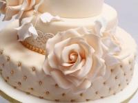 Cukura lapiņas, pērlītes un ziedi uz kāzu tortes