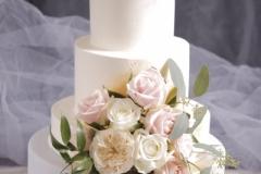 4- stāvu kāzu torte ar rozēm. Dažāds stāvu augstums. Apakšējais stāvs pārklāts ar cukura masu, pārējie ar sviesta krēmu.