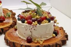Biskvīta kazu torte ar ogām. Torte uz koka ripas. Lauku torte ar zemenēm