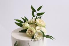 Zaļumi un baltas rozes kāzu tortei. Kāzu saldumi.