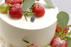 Kailā kāzu torte ar ogām. Biskvīta kūka ar vārīto krēmu un avenēm. Ogu dekors.