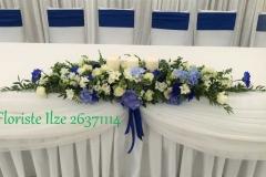 Jaunlaulāto galda ziedu dekors no baltiem un ziliem ziediem. Kāzas Riverside House