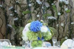 Viesu galda dekors uz ziedu sienas fona. Reiņa trase