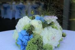 Ziedu kompozīcijas uz āra galdiņiem. Reiņa trase