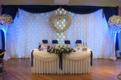 Kāzu noformējums zilos toņos. Ziedu kompozīcija uz jaunlaulāto galda. Royal blue