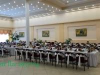 Ziedu kompozīcijas augstās vāzēs uz viesu galdiem