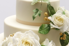 Kāzu torte ar baltām cukura rozēm un zaļumiem