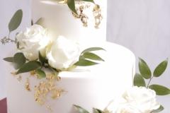 Kāzu torte ar cukura masas pārklājumu, baltām rozēm un zeltu.