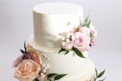 Klasiska vaniļas krēma torte pārklāta ar sviesta krēmu un dekorēta ar dzīvajiem ziediem.