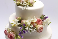 Krāsains ziedu dekors uz kāzu tortes