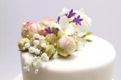 Kāzu torte pārklāta ar cukura masu un dekorēta ar dzīvajiem ziediem
