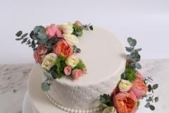 Biskvīta torte ar vaniļas krēmu. Svaigas ogas. Pērles, ziedi kāzu tortes dekorā.