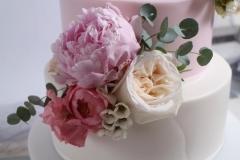 Baltas angļu rozes uz biskvīta kāzu tortes. Bagātīgs ziedu dekors.