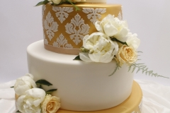 Kāzu tortei mirdzošs zelta stāvs ar baltiem reljefa rakstiem