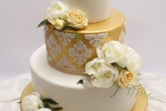 Dzīvo ziedu un zelta dekors kāzu tortei
