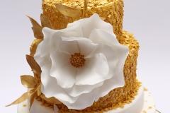 Kāzu torte ar cukura masas pārklājumu, cukura ziedu un zelta lapiņām