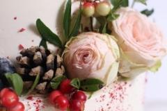 Biskvīta kāzu torte ar rožu un meža ogu dekoru.