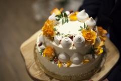 Viegla, kremīga kāzu torte ar kraukšķi. Dzīvo ziedu un bezē dekors