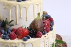 Kāzu torte ar baltās šokolādes notecējumiem un ogu dekoru.