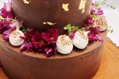 Šokolādes kūka arsokolādes krēmu, rumu un ķiršiem. Dzīvo ziedu dekors, zelts.