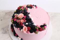 Neliela rozā kāzu torte. Torte pārklāta ar sviesta krēmu un ogām.