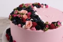Vasarīgi ziedi un ogas uz rozā kāzu tortes. Biskvīta torte.