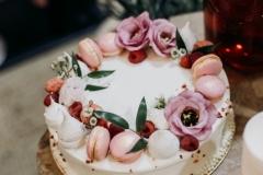 Kāzu torte ar makarūniem, ziediem un ogām.